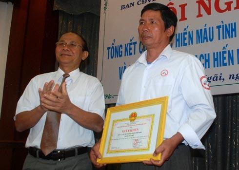 Ông Nguyễn Ngọc Giao (cầm bằng khen) được Ban chỉ đạo vận động hiến máu Quảng Ngãi tôn vinh hôm 22/12. Ảnh: Trí Tín