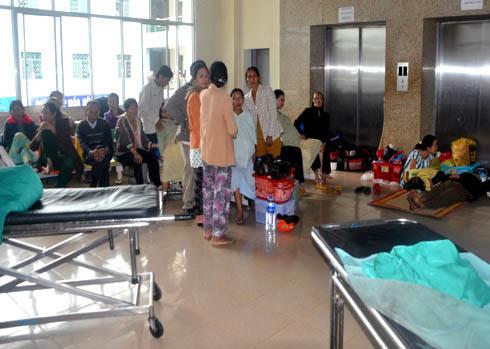 Khu vực trước phòng Sinh, khoa Sản, Bệnh viện đa khoa Quảng Ngãi lúc nào cũng đông nghẹt người. Người ngồi trên ghế, trải chiếu ngồi, nằm la liệt dưới đất bên cạnh chân cầu thang máy.Ảnh: Trí Tín