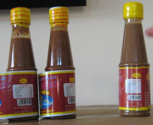Chai mắm nêm giả (bên phải) so sánh với hai chai thật (bên trái). Ảnh: Tùy Phong.